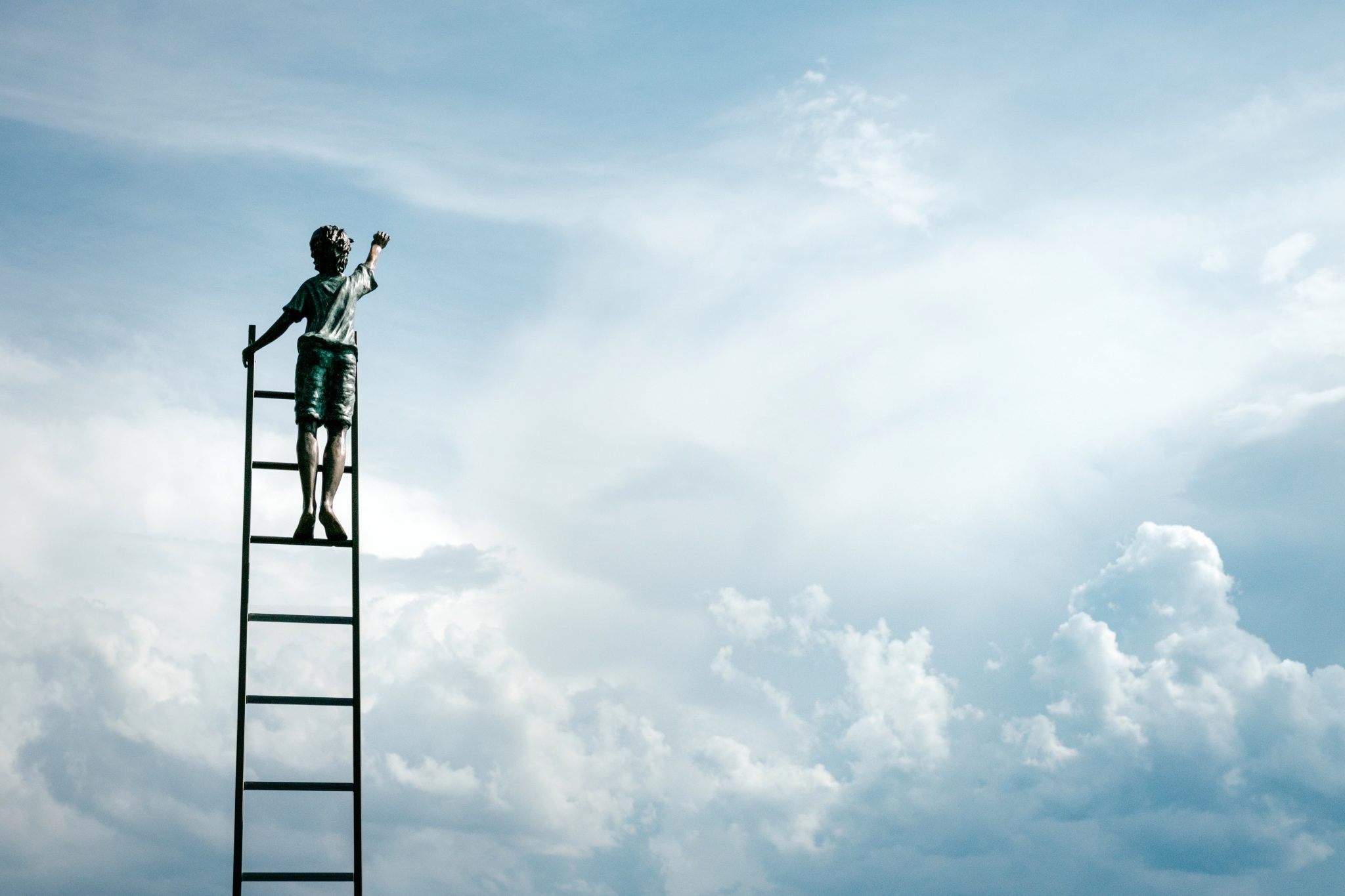 Man climbing a ladder into the clouds